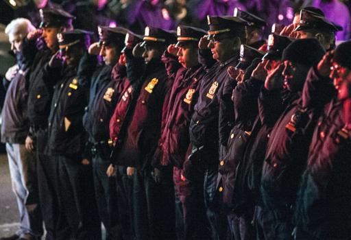 Poliziotti sull'attenti mentre passa un mezzo con i corpi degli agenti ufficiali (Reuters)