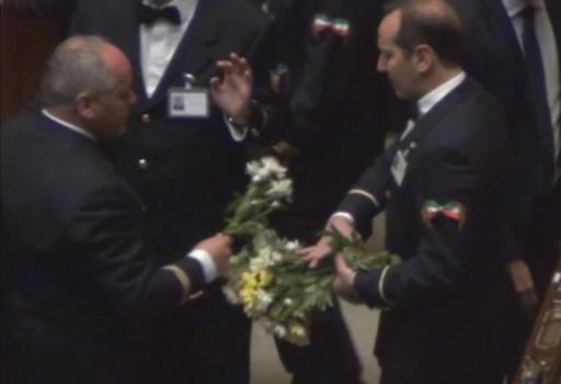 Un commesso della Camera raccoglie i crisantemi lanciati dai deputati di Sel