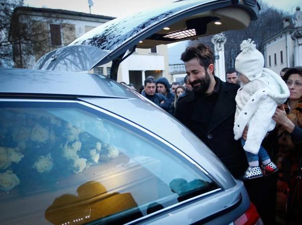 Brescia, il marito di Giovanna Lazzari ai  funerali della donna, morta a 30 anni all'ottavo mese di gravidanza, con uno dei due figli (Lapresse)