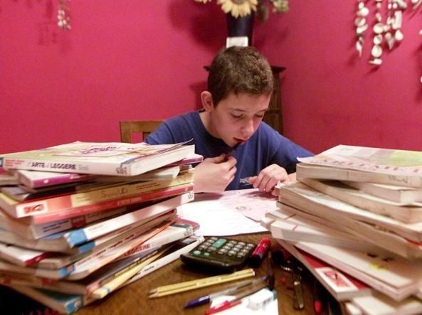 Uno studente e i libri di scuola impilati l'uno sull'altro. Talvolta ridursi all'ultimo nello studio o nella consegna di un testo non � sbagliato... (Fotogrammabrescia)