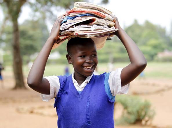 Un bambino kenyano con plichi di quaderni e fotocopie sulla testa (Reuters)