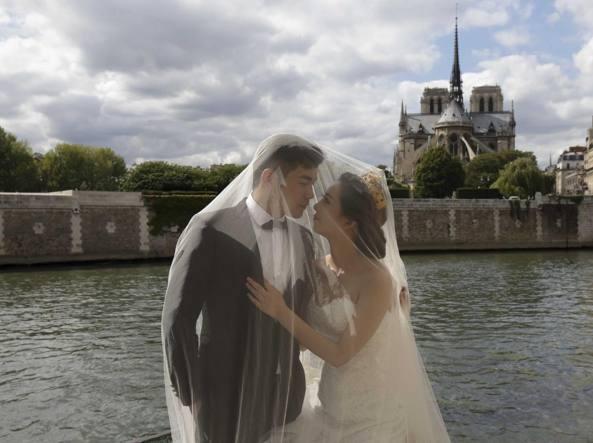 Sposi cinesi in abiti nuziali occidentali sulla Senna, a Parigi (Reuters)