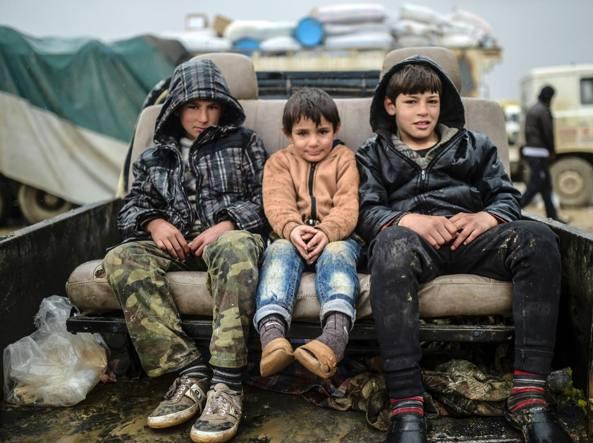 Bambini in fuga da Aleppo a bordo di un pick up vicino al campo profughi di Bab al Salam (Afp)