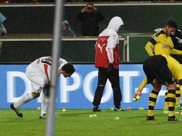 I giocatori dello Stoccarda e del Borussia Dortmund raccolgono le palline da tennis lanciate dai tifosi del Borussia per protestare contro il caro-biglietti (Epa/Murat)