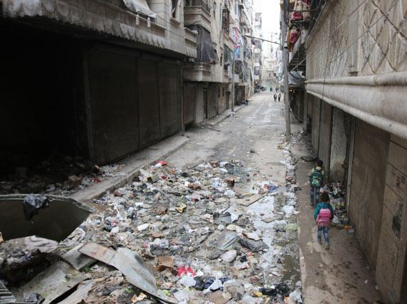 Le macerie di Aleppo. Sul  marciapiede, due bambini vanno a scuola (foto Ap)