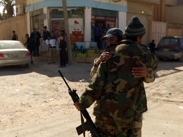 L'abbraccio di due soldati fedeli al governo di Tobruk dopo aspri combattimenti per strappare all'Isis il controllo di Bengasi (Afp)