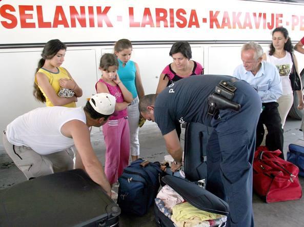 Un poliziotto albanese controlla i bagagli dei passeggeri di un pullman al confine con la Grecia (Reuters)