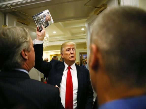 Trump mostra il suo libro durante una conferenza stampa in Florida (Afp)