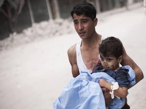 Un ragazzo siriano tiene in braccio un bambino ferito ad Aleppo (foto Ap /Manu Brabo)