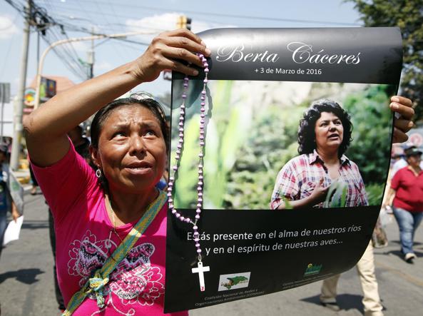 Una donna con il santino di Berta Caceres, attivista e fondatrice del Copinh (Ap)