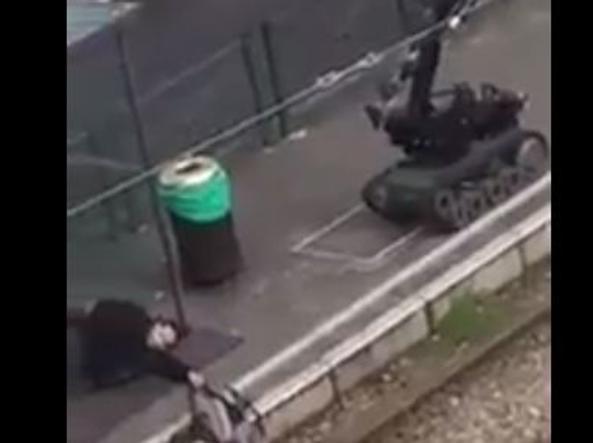 Un robot degli artificieri si avvicina ad un uomo a terra, ferito dagli agenti