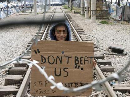 Un ragazzino  espone un cartello: «Non picchiateci»