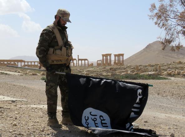Un soldato lealista riavvolge la bandiera dello Stato Islamico a Palmira (Afp)