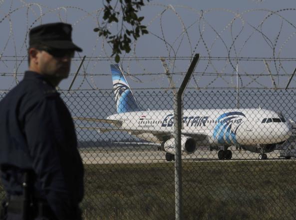 Un agente all'aeroporto di Larnaca, Cipro, davanti all'aereo dirottato (Reuters)