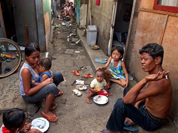 Una famiglia povera consuma un pasto per strada nella baraccopoli di Tanah Abang, nei pressi di Giakarta, in Indonesia (foto Ap/David Longstreath)