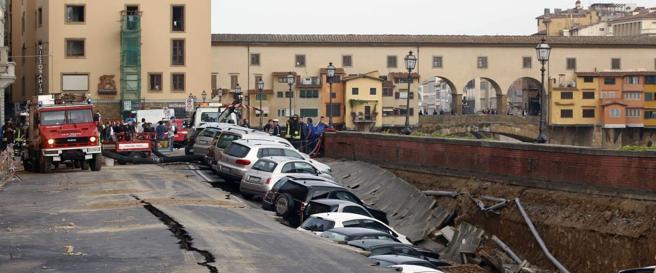La voragine di 200 metri che ha inghiottito le macchine e, alle spalle, il Ponte Vecchio (Olycom)