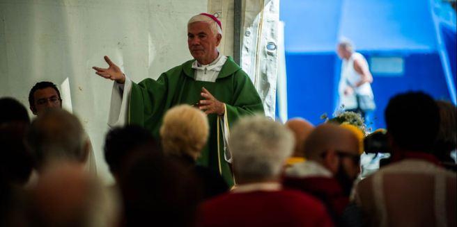 Il vescovo Giovanni D'Ercole celebra  messa nella tendopoli di  Pescara del Tronto (Fotogramma)