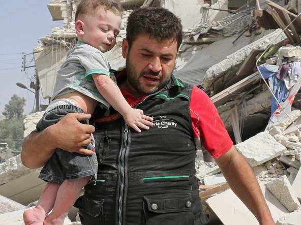 Un bimbo soccorso ad Aleppo (Afp)