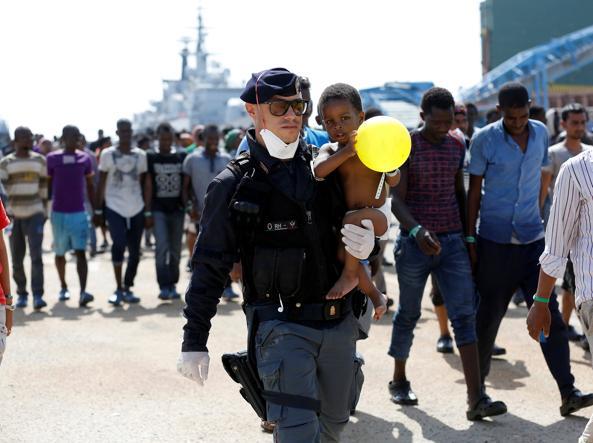 Un poliziotto italiano con un bimbo in braccio al porto di Augusta in Sicilia (Reuters)