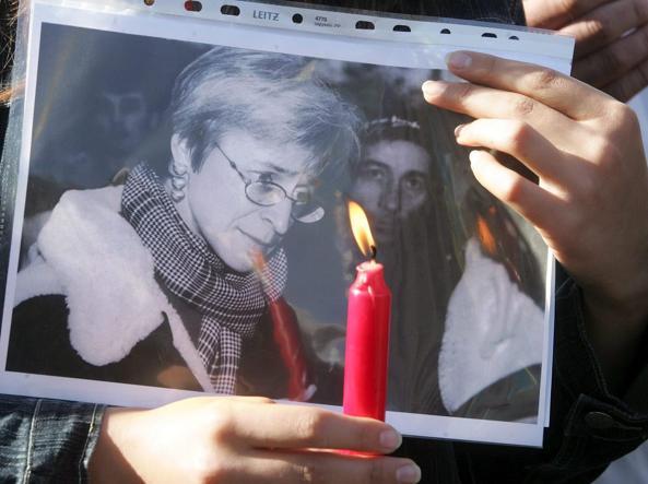 Una candela a Kiev, davanti all'ambasciata russa di fronte all'immagine della giornalista uccisa (Ansa)