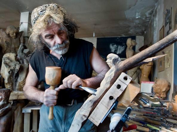 Mauro Corona (Baselga di Piné, Trento, 1950) nella sua bottega di scultore. Oltre che romanziere, infatti, è anche artista e alpinista (foto Obiettivo)