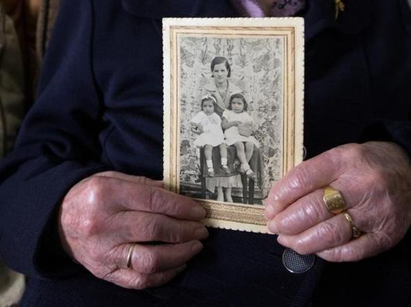 Esperanza Fernandez, 103 anni, con la foto di quando era giovane con le sue figlie (Reuters/Andrea Comas)