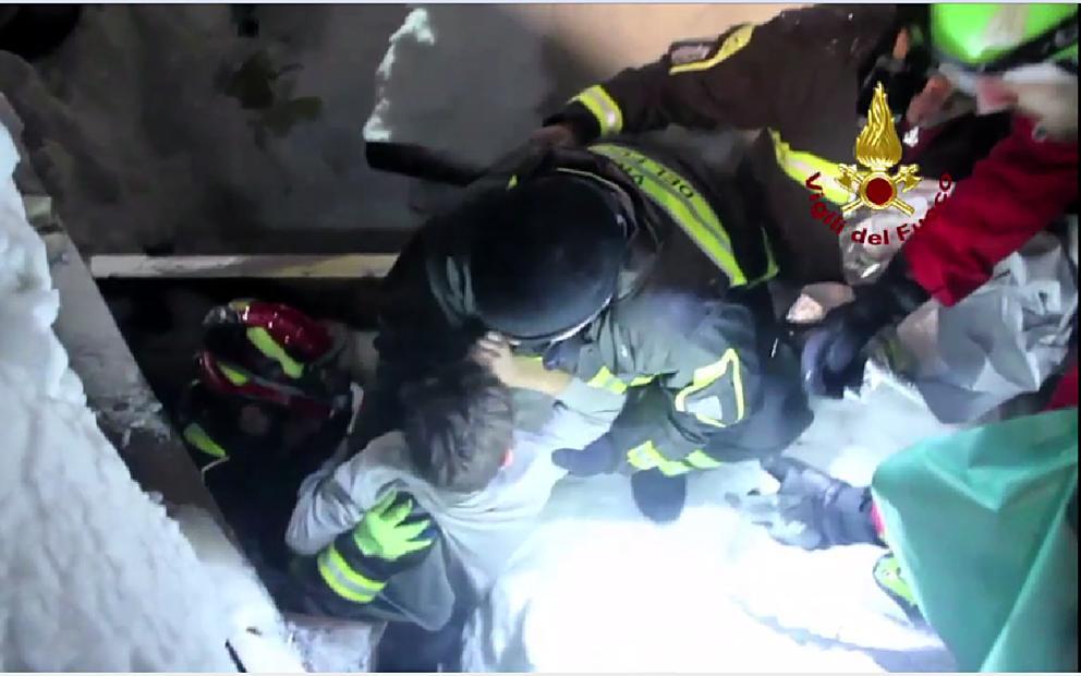 Il momento in cui i Vigili del fuoco estraggono dall'hotel uno dei bambini intrappolati (Afp)
