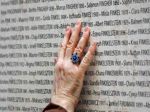 Una mano tocca i nomi e gli anni di nascita delle vittime francesi della persecuzione nazista, che sono incisi su un muro nel Memoriale della Shoah a Parigi (foto Afp / Joel Saget)