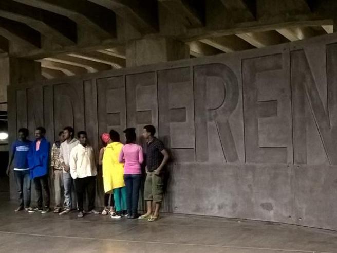 I profughi ospitato al Memoriale della Shoah davanti alla scritta «Indifferenza»