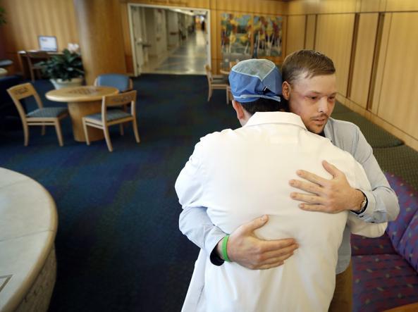 Lìabbraccio tra Andy Sandness e il chirurgo Samir Mardini della Mayo Clinic che gli ha ridato un volto nuovo (AP)
