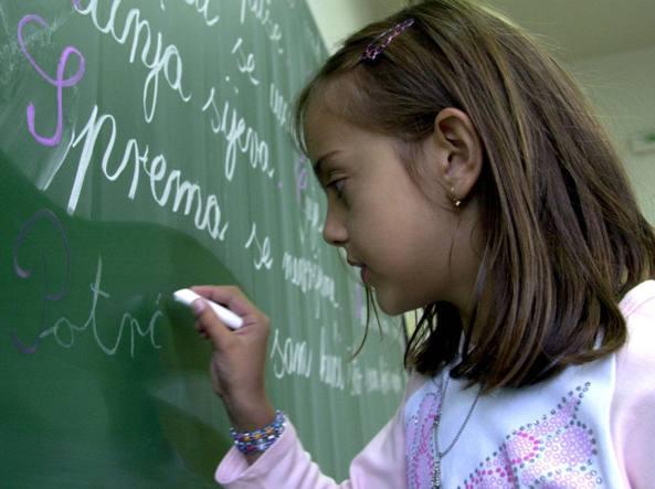 Indira Paratusic, bambina di nove anni, scrive sulla lavagna in una scuola della Bosnia nel 2003 (foto Ap/Sava Radovanovic)
