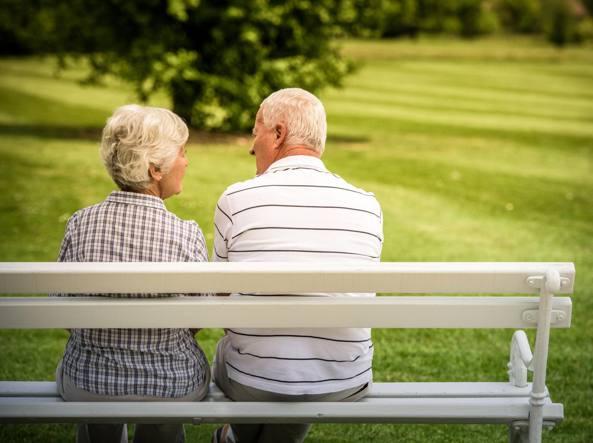coppia di anziani di spalle, seduta su una panchina in un parco