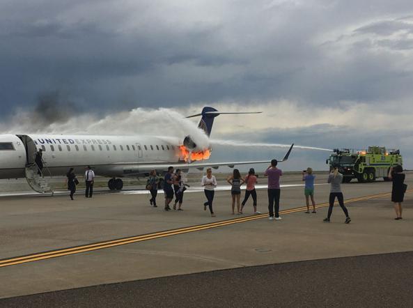 6 luglio 2017: il motore di un velivolo brucia subito dopo l'atterraggio all'aeroporto di Denver (Usa), ma diverse persone si fermano per scattare foto e registrare video dell'incidente (foto di Jeannette Jakus)