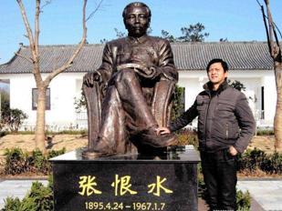 Liu Yongbiao (53 anni) di fianco alla statua