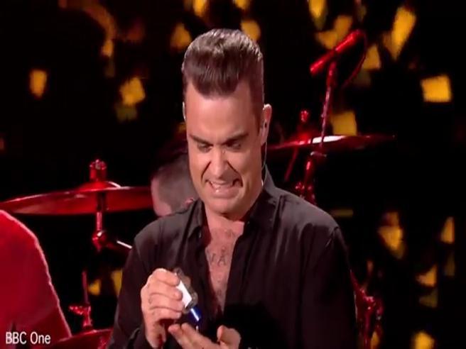 Robbie Williams allo spettacolo di Capodanno stringe le mani, ma poi si disinfetta....