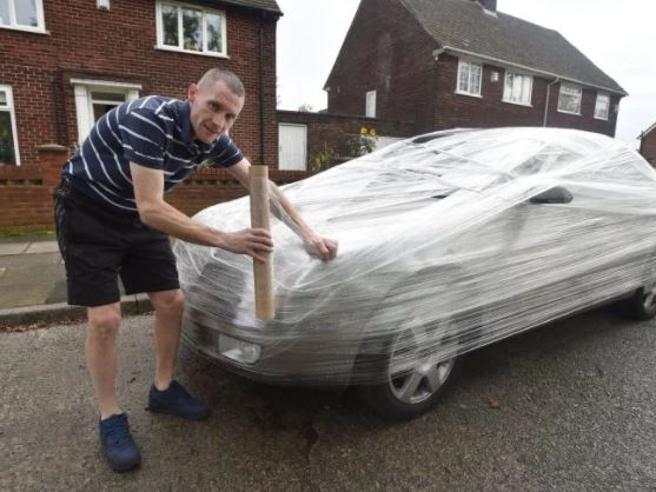 Gli parcheggia l'auto davanti casa, lui per dispetto gliela impacchetta con la pellicola