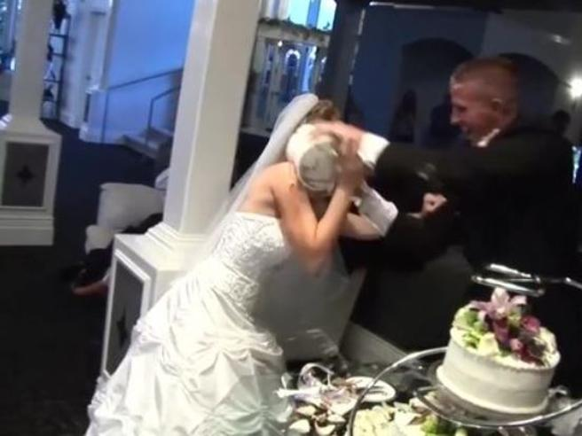 Lo sposo tira la torta alla sposa durante il banchetto nuziale