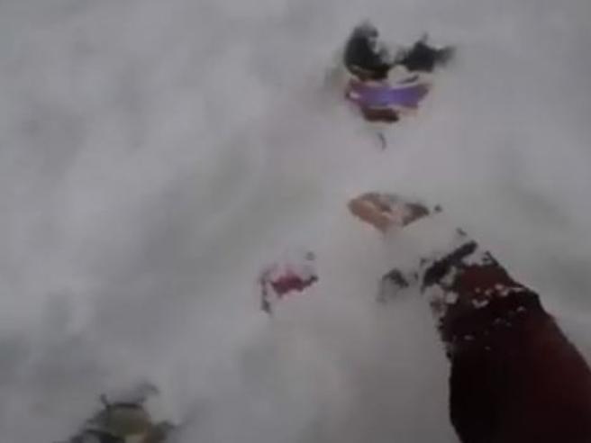 Snowboarder salta e resta sommerso sotto la neve l'amico scava con le mani e lo salva