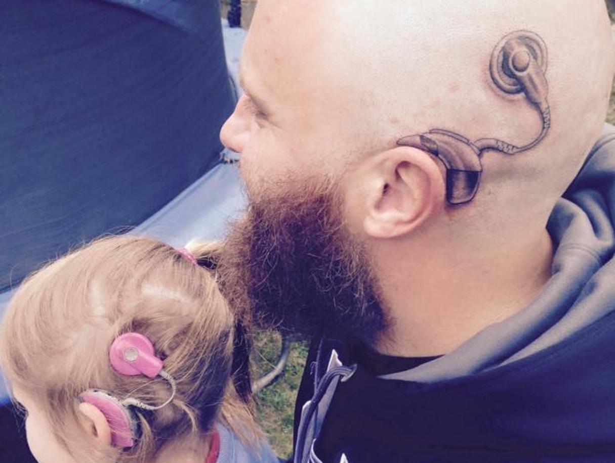 La figlia porta l'apparecchio acustico, papà Alistair si rasa e se lo tatua