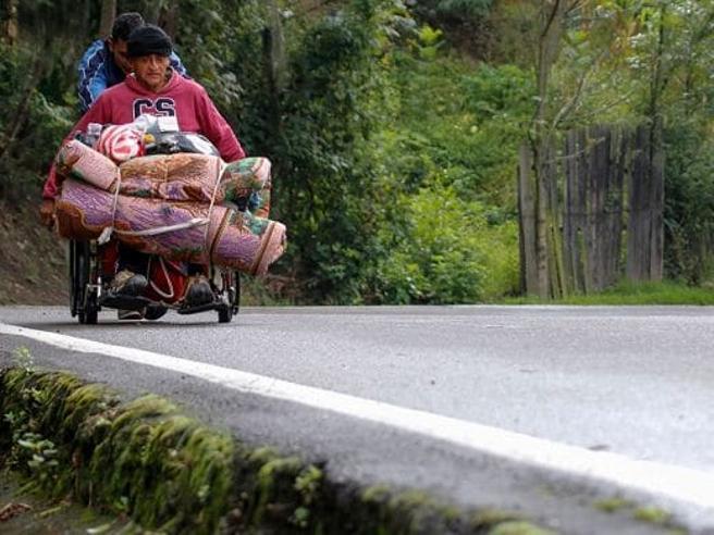 Fuga dal Venezuela in sedia a rotelle: il figlio spinge il padre in Colombia in cerca di medicine