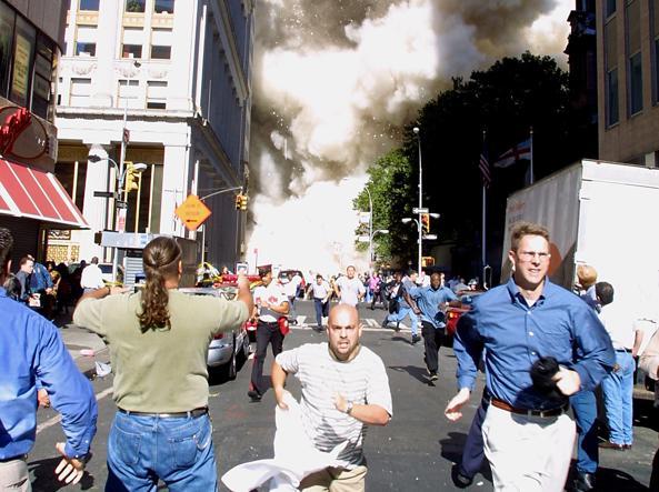 Il panico sui volti di un gruppo di passanti in fuga durante il crollo delle Torri (Getty)