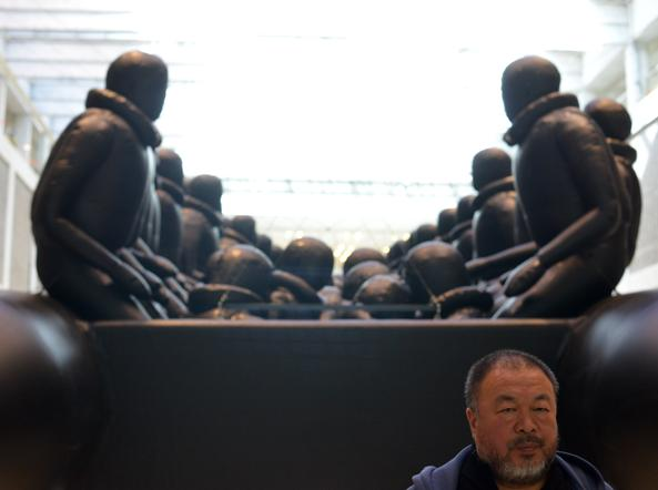 Ai Weiwei davanti all'opera «The law of the journey» (La legge del viaggio): tra le installazioni più imponenti dell'artista, invita a riflettere sul tema immigrazione. Su un gommone di 70 metri siedono 278 sculture di rifugiati senza volto (foto Getty)
