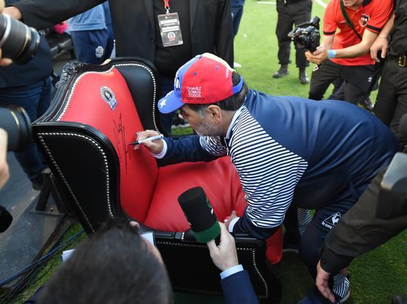 Maradona firma la poltrona-trono regalatagli a Rosario, dove era stato accolto in maniera speciale dai tifosi del Newell's Old Boys: una panchina speciale per l'ex numero 10, dalla quale ha guidato i suoi giocatori del Gimnasia La Plata