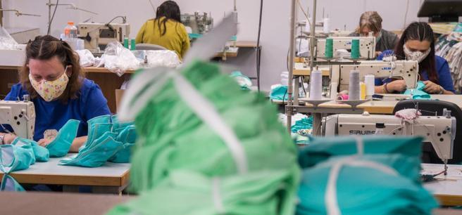 Un laboratorio tessile riconvertito alla produzione di mascherine  (foto Imagoeconomica)