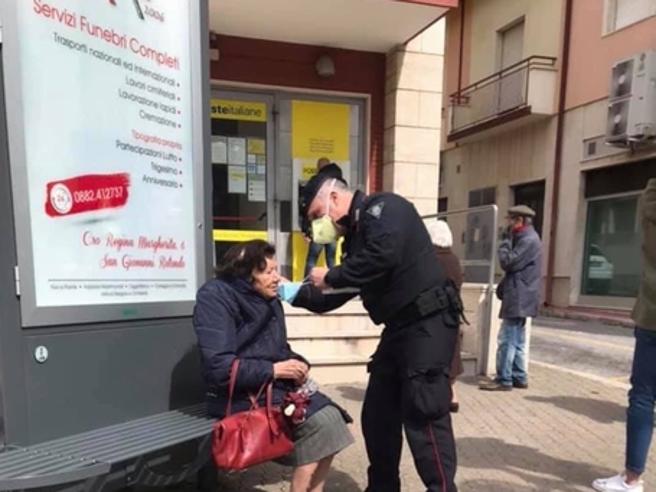 Coronavirus, il carabiniere che mette la mascherina all'anziana. «È quello che mi dice la divisa»