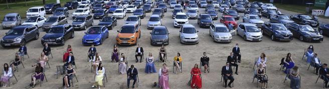 Consegna del diploma in un liceo tedesco, con le famiglie in attesa nelle auto parcheggiate