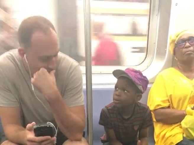 New York, passeggero lascia il suo smartphone a un bambino per giocare. Il video che commuove la Rete