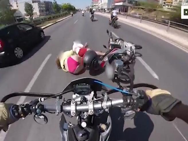 Incidente ad Atene, coppia di motociclisti (senza casco) sull?asfalto dopo un urto