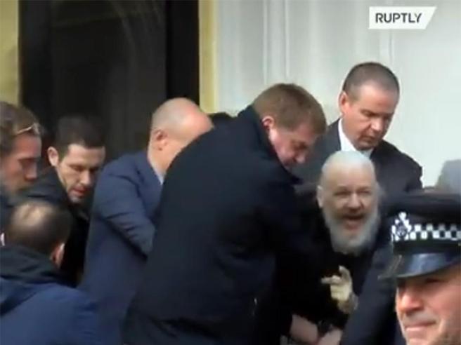 Pallido e con la barba lunga: l'arresto di Julian Assange portato via  a forza |   Video