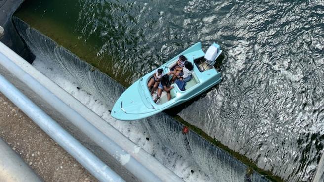 Barca con quattro donne a bordo bloccata in bilico su una diga